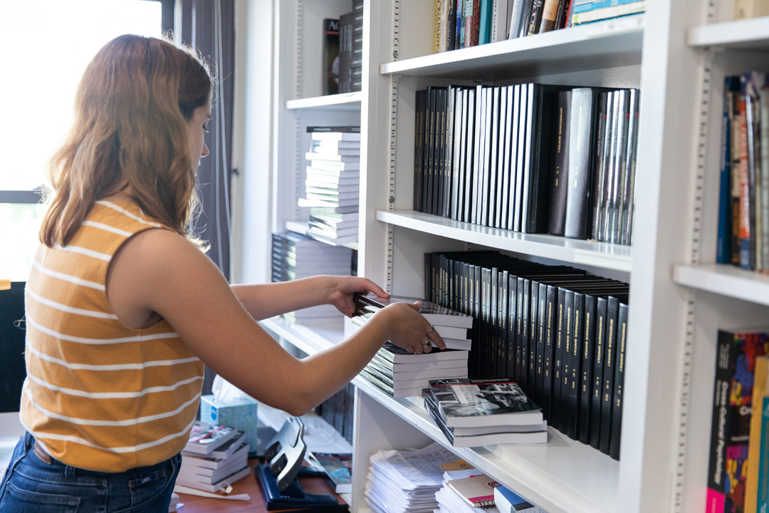 An anthropology student rearranging books