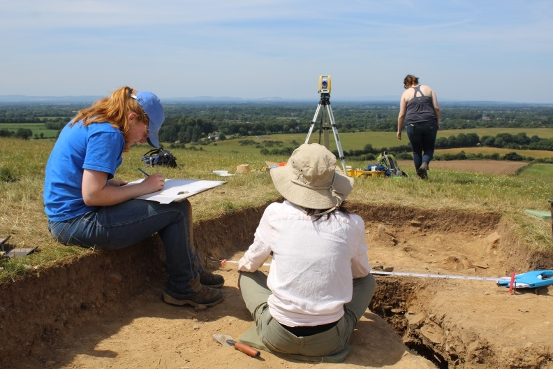 A student writes on a notepad at Dun Ailinne while two others walk around the dig site