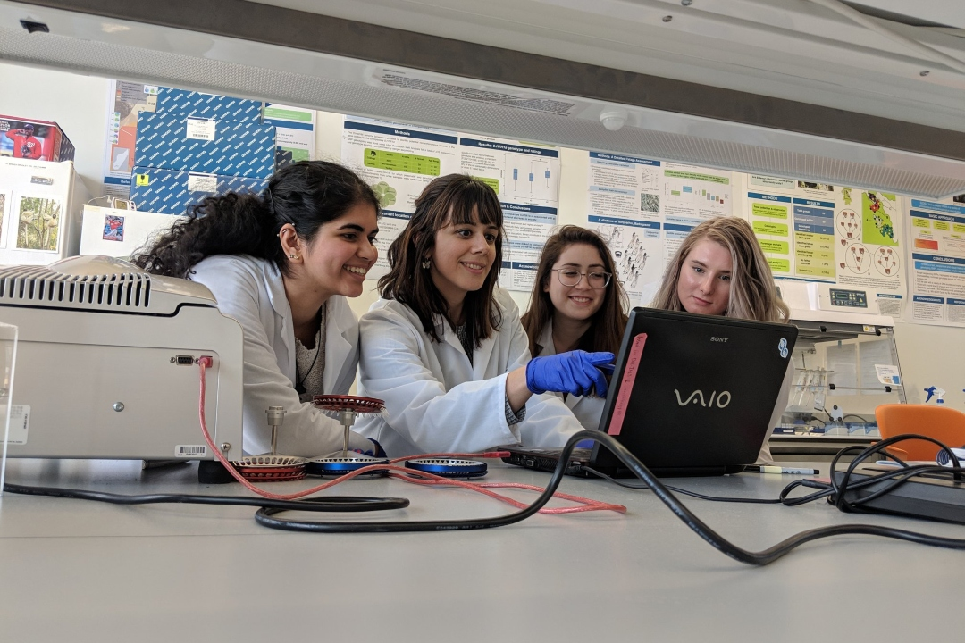 Four female students in lab coats looking at a laptop