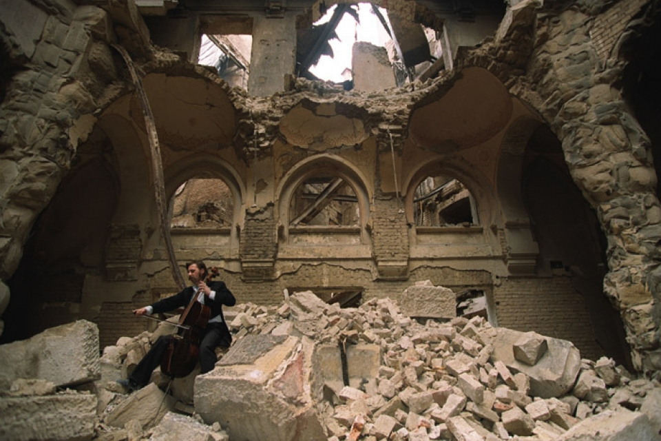 Bosnian cellist Vedran Smailovic plays an elegy in Sarajevo's blasted and burned library. Mikhail Evstafiev/Wikimedia Commons